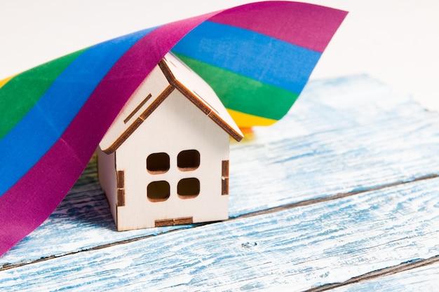 Drewniany model domu stoi na niebieskiej drewnianej powierzchni
