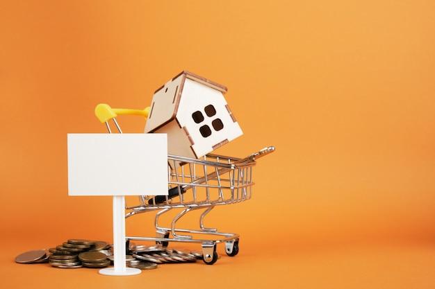 Drewniany model domu w koszyku, biały pusty znak i monety na brązowym tle