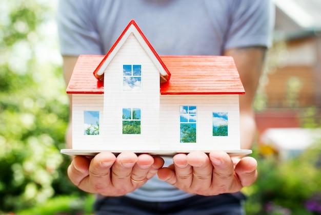 Drewniany model domu w rękach, lato na zewnątrz, nowa koncepcja domu