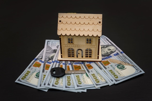 Drewniany model domu z banknotami dolarowymi i kluczem