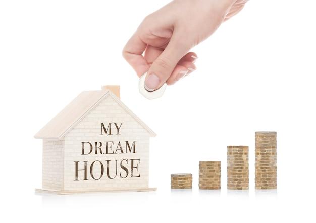 Drewniany model domu z monetami obok i ręką
