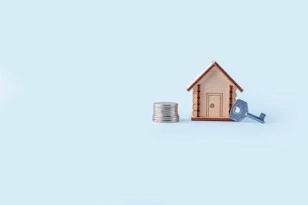 Drewniany model domu, zapasy pieniędzy i klucz na niebieskim tle. koncepcja kupna i sprzedaży domów i nieruchomości. ubezpieczenie domu, nieruchomości i hipoteka. skopiuj miejsce na tekst