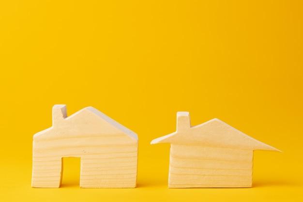 Drewniany model mini dom na żółtym tle z bliska