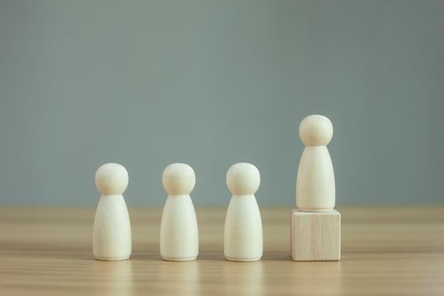 Drewniany model osoby wśród ludzi na czarnym tle