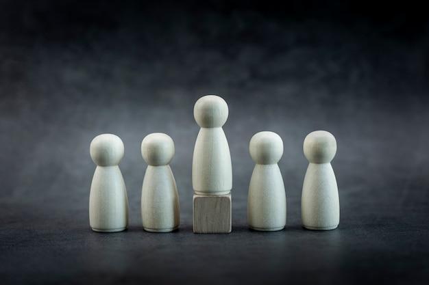 Drewniany model osoby wśród ludzi na pastelowym czarnym tle koncepcja przywództwa