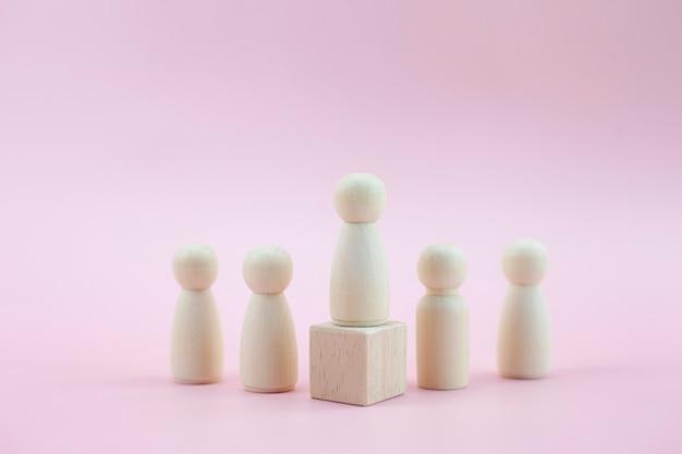 Drewniany model osoby wśród ludzi na pastelowym różowym tle