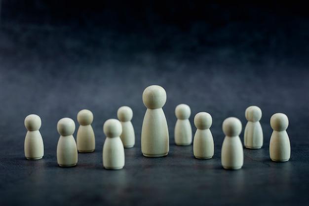 Drewniany model osoby wśród małych ludzi na czarnym tle