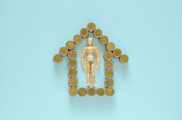 Drewniany model pozostaje pośrodku monet bahtów tajskich, które są symbolem domu.