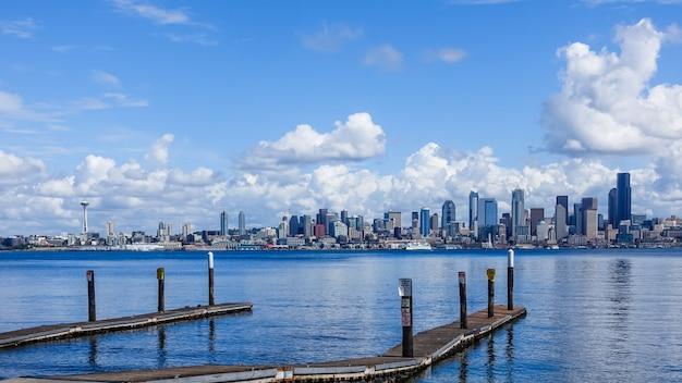 Drewniany molo nad morzem z miastem seattle, usa pod pięknymi chmurami