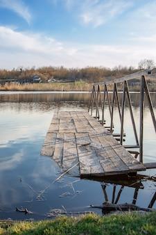 Drewniany most na jeziorze. świt nad wodą. spokojna atmosfera w przyrodzie.