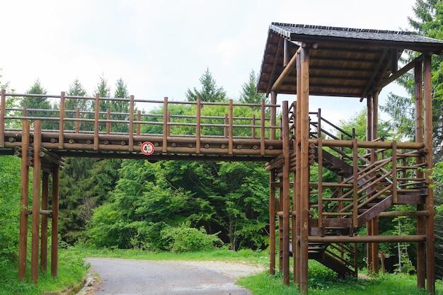Drewniany most nad drogą wzdłuż ścieżki trekkingowej we włoskich alpach