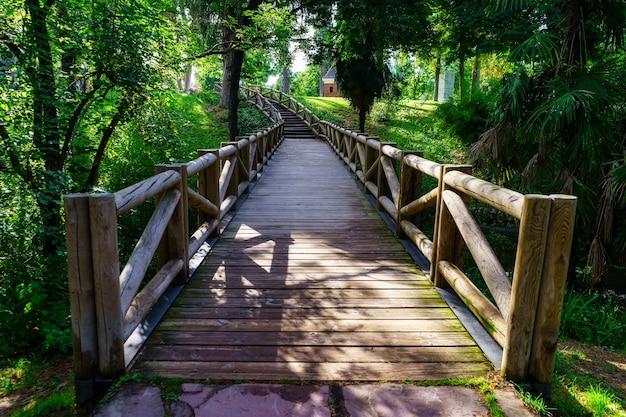 Drewniany most nad małym strumieniem w publicznym parku retiro w madrycie.