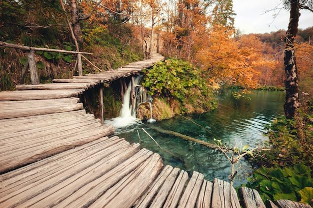Drewniany most przez rzekę w sezonie jesiennym