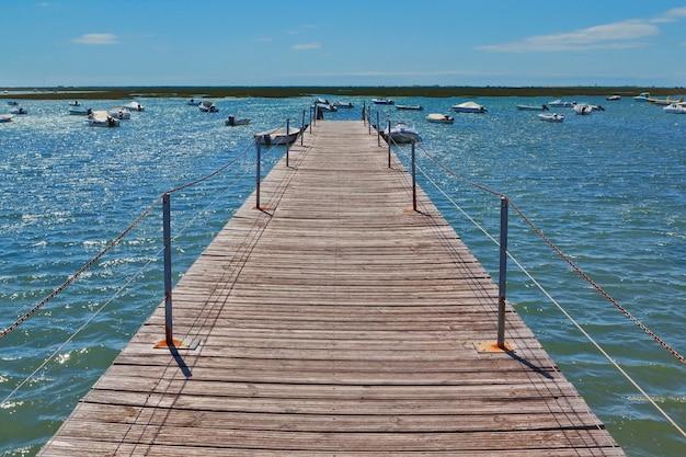 Drewniany most w porcie na morzu przed łodziami.