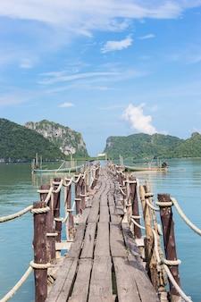 Drewniany most wystający w morze z dwiema łodziami z długim ogonem na morzu i jasnym błękitnym niebem