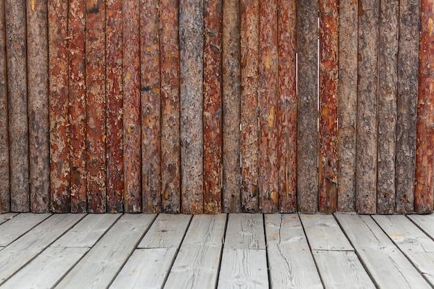Drewniany mur. starodawny stary mur wykonany z brązowych i czerwonych desek na deskach.
