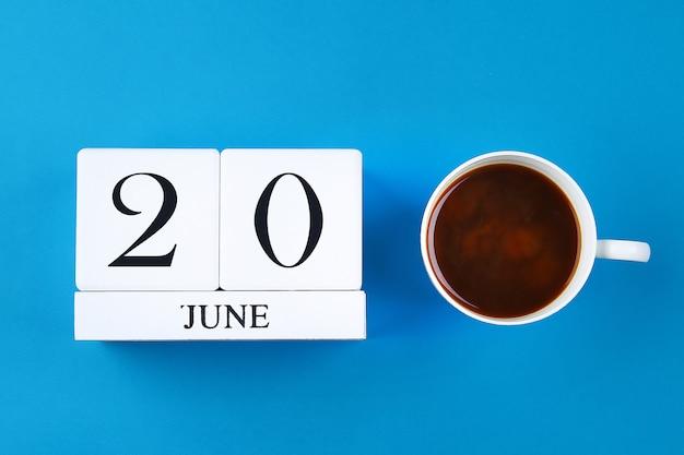 Drewniany notes z datą 20 czerwca i kubkiem do kawy na pastelowym niebieskim tle.