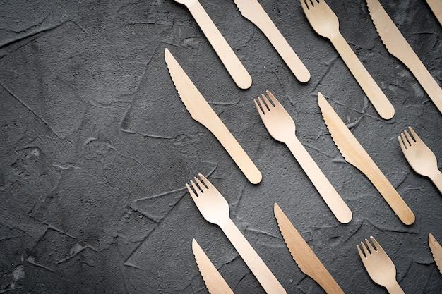 Drewniany nóż i widelec na czarnym tle. ekologiczna koncepcja zero odpadów. widok z góry z miejscem na tekst. skopiuj miejsce