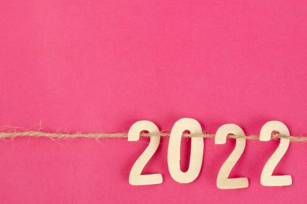 Drewniany numer 2022 i lina na różowym tle z miejscem na kopię tekstu lub wiadomości.