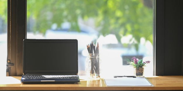 Drewniany obszar roboczy otacza laptop komputerowy, wazon z ołówkami, roślina doniczkowa i schowek.