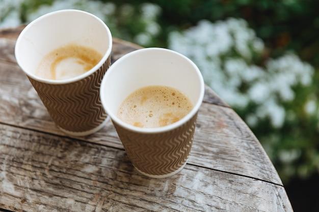 Drewniany okrągły stół z kilkoma papierowymi brązowymi kubkami świeżej gorącej kawy