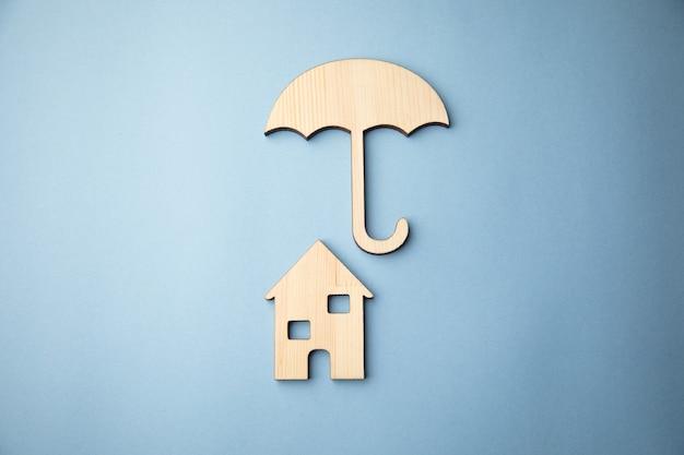 Drewniany parasol z modelem domu na stole