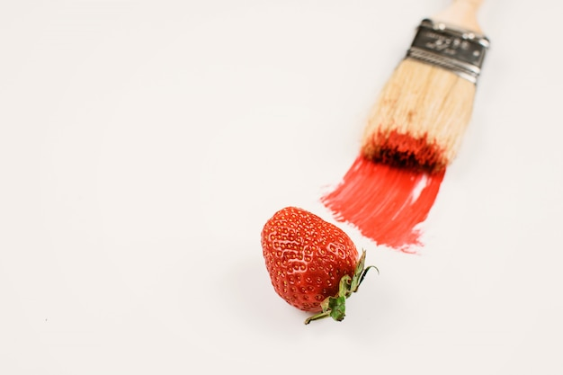 Drewniany pędzel do malowania z czerwoną farbą i czerwoną świeżą truskawką