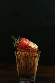 Drewniany pędzel do malowania ze złotą farbą i czerwoną świeżą truskawką na czarno.