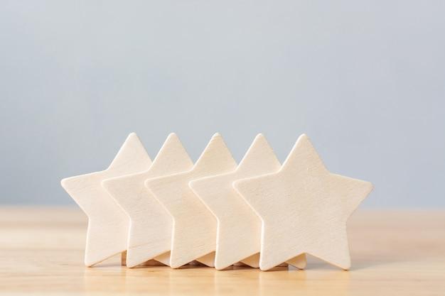 Drewniany pięciogwiazdkowy kształt na stole. najlepsza koncepcja doskonałej jakości usług biznesowych oceniana na podstawie doświadczenia klienta