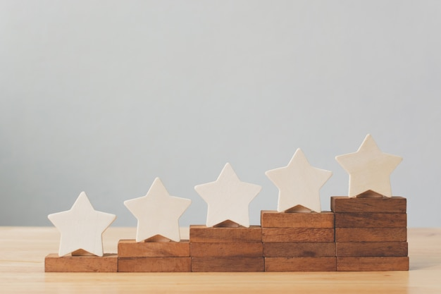 Drewniany pięciogwiazdkowy kształt na stole. najlepsze doskonałe usługi biznesowe oceniające koncepcję obsługi klienta