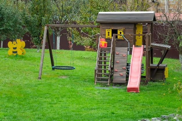 Drewniany plac zabaw z plastikowymi elementami huśtawki i zjeżdżalnie dla dzieci w ogrodzie