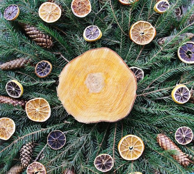 Drewniany plasterek na zielonych gałęziach jodły ozdobiony suszonymi plasterkami pomarańczy i szyszkami. boże narodzenie i nowy rok rocznika zimowych świąteczna kompozycja.