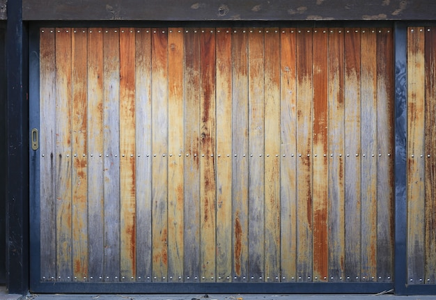 Drewniany płot na tle ściany. stare drewniane deski drzwiowe