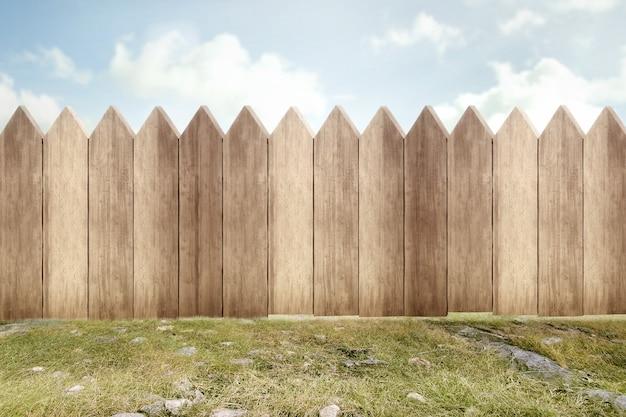 Drewniany płot na zielonym ogrodzie z błękitnym niebem