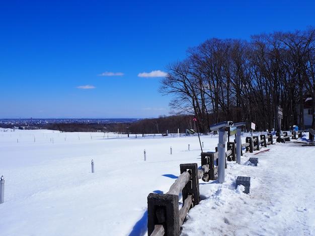 Drewniany płot oddziela obszar śniegu.