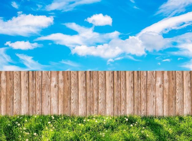 Drewniany płot ogrodowy na podwórku i błękitne niebo z białymi chmurami