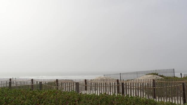 Drewniany płot piaszczysta mglista plaża california usa pacific ocean coast mgła mgła na brzegu morza