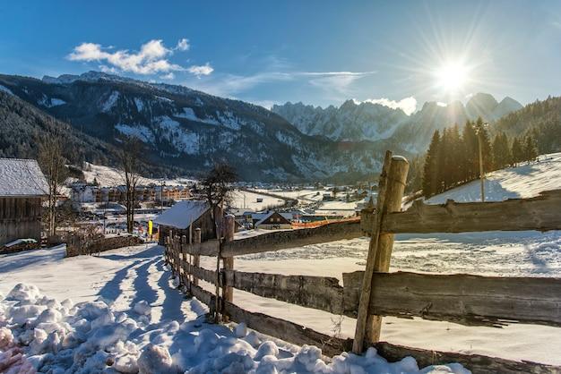 Drewniany płot w zaśnieżonym polu. stary, szary płot na śniegu. słoneczny dzień i stary płot