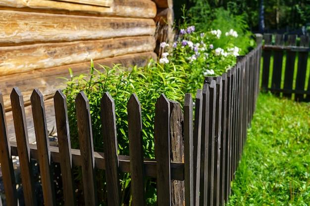 Drewniany płot z ogrodem i świeżymi wiosennymi kwiatami.