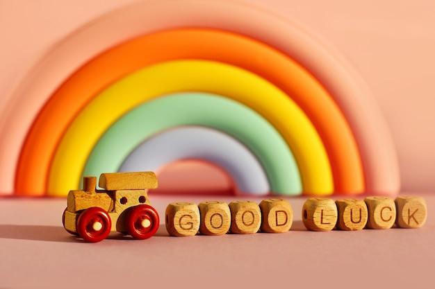 Drewniany pociąg z kostkami z napisem powodzenia na tle obszernej jasnej tęczy