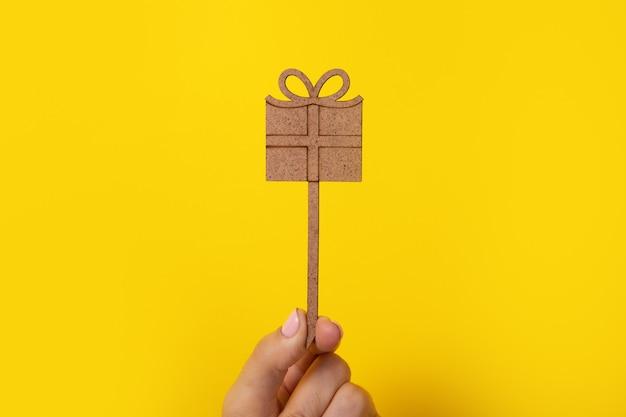 Drewniany prezent w ręku na żółtym tle