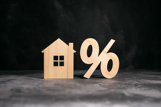 Drewniany procent z modelem domu na szarym tle