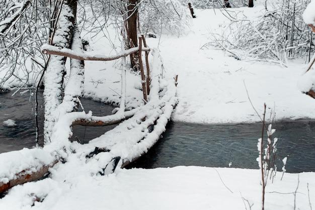 Drewniany prowizoryczny most nad stawem. zimowy las. wiejski krajobraz