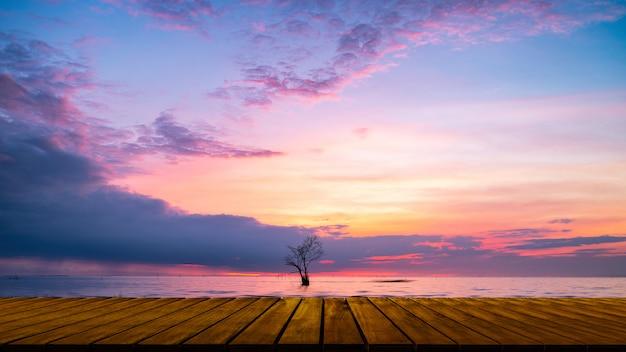 Drewniany przejście z osamotnionym drzewem w jeziornym i kolorowym niebie przy pak pra wioską, pha