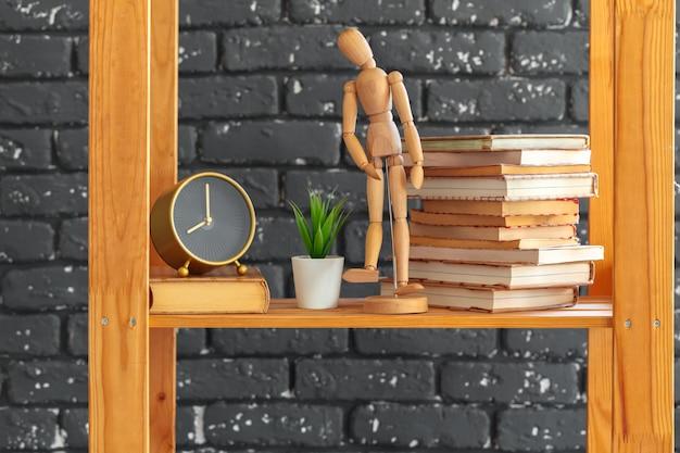 Drewniany regał z książkami i innymi rzeczami na czarnym murem