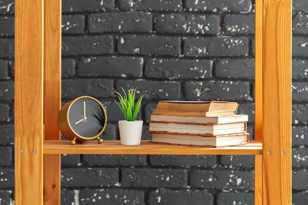 Drewniany regał z książkami i innymi rzeczami pod czarnym murem