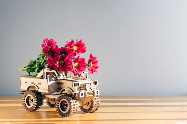 Drewniany samochód z kwiatami na lekkim tle z odbitkową przestrzenią