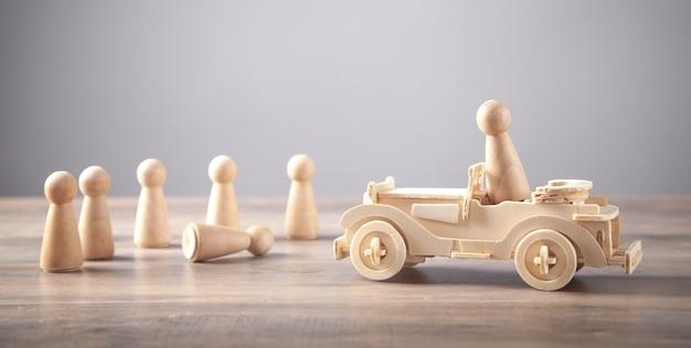 Drewniany samochodzik i postacie ludzkie. wypadek drogowy