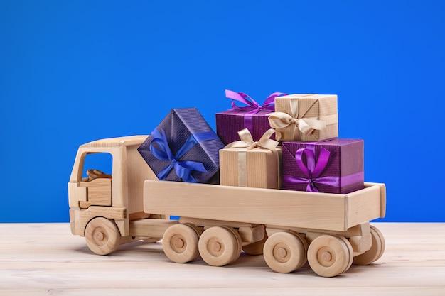 Drewniany samochodzik z prezentami. pudełka w świątecznym opakowaniu.