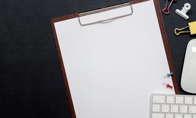 Drewniany schowek z pustą makietą papieru i białą klawiaturą komputerową na czarnej skórze